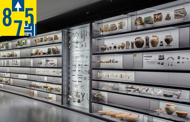 Das Bild zeigt die über 40 Meter lange Vitrinenwand mit Funden aus dem Mittelalter.
